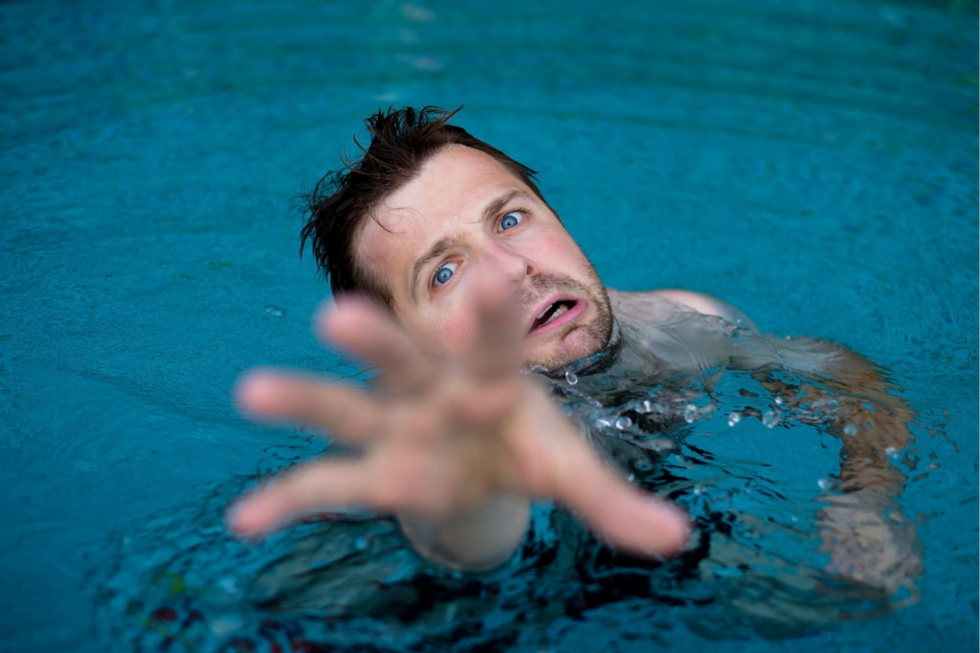 Drowning man desperately reaching for help.