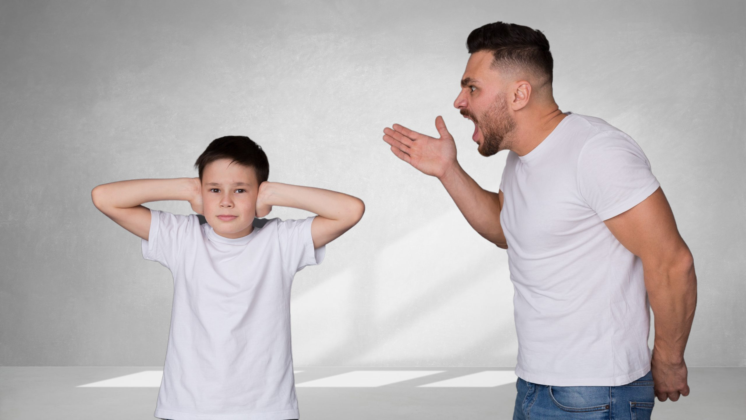 Father yelling at son, son covers his ears.