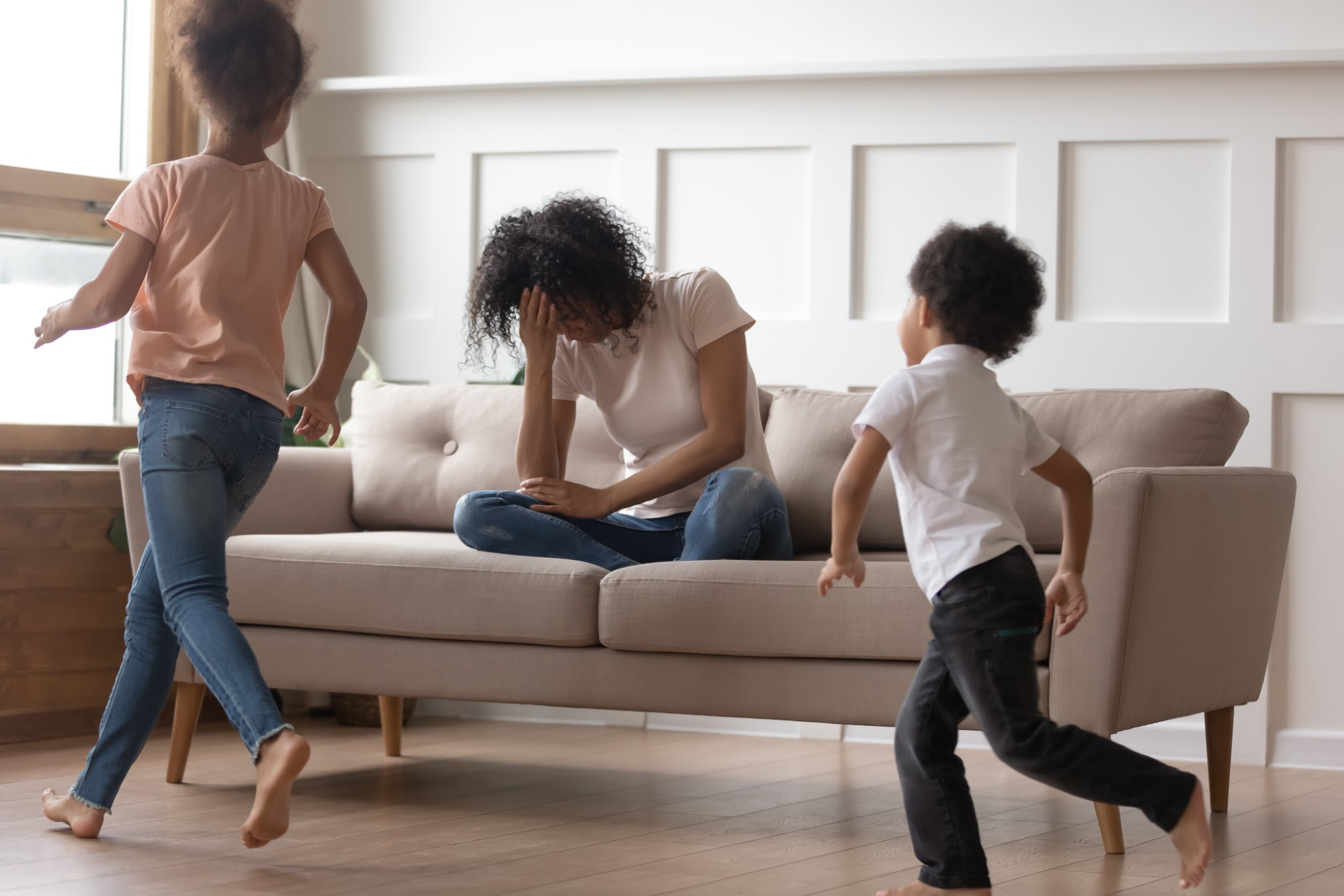 In living room mixed-race mother sit on couch cover face with hand feels desperate unhappy can't handle with noisy kids running near and make noise, misbehave children, exhausted mom need rest concept