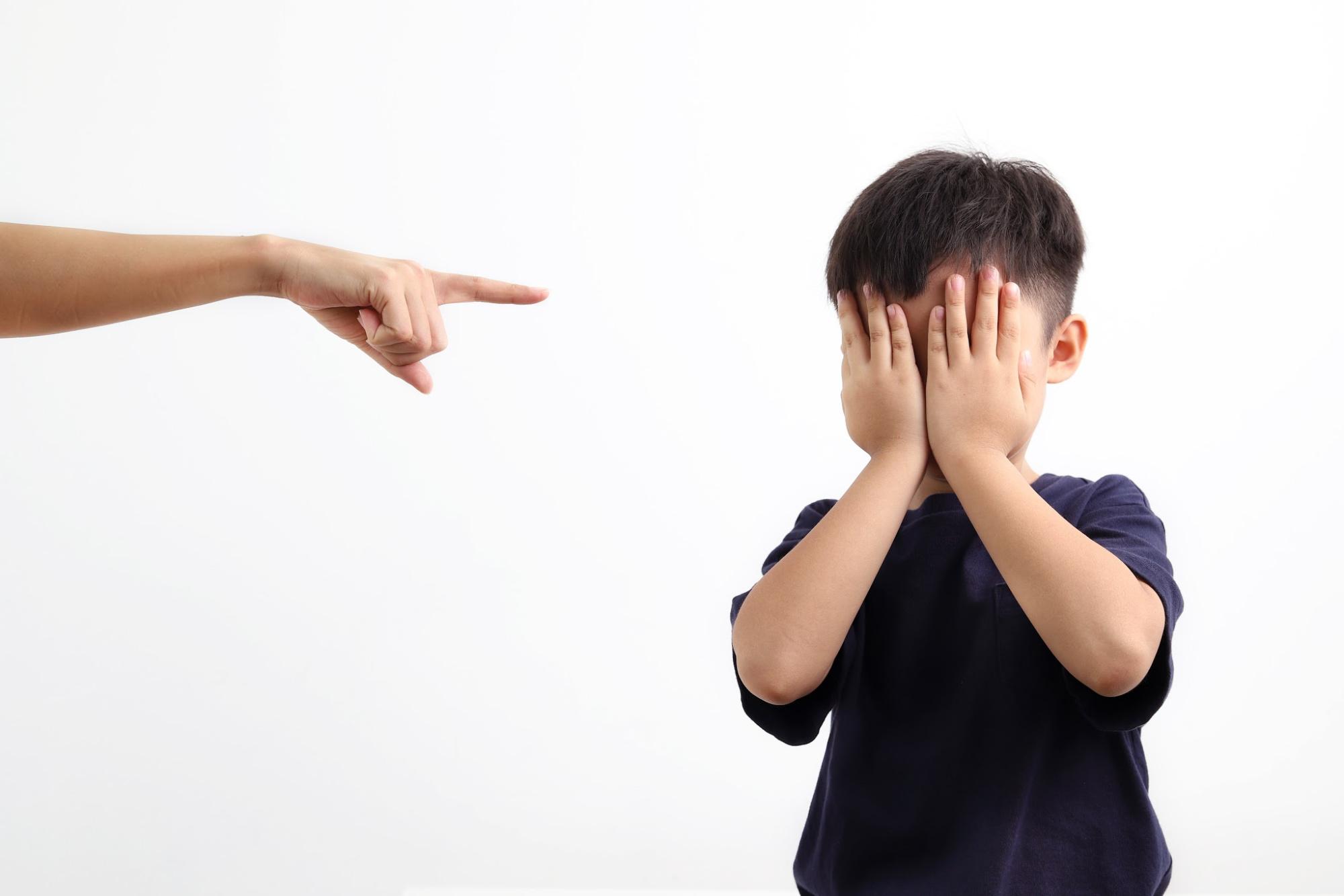 Arm of parent scolding scared little boy.