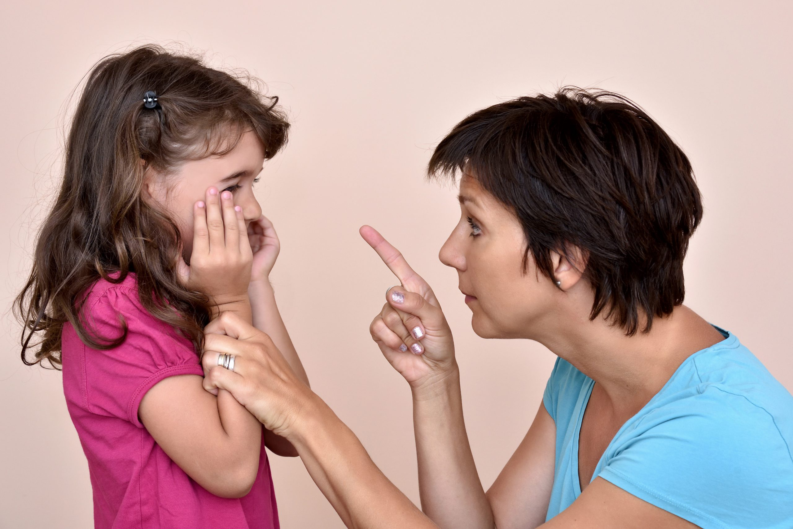 Mother scolding scared little girl.
