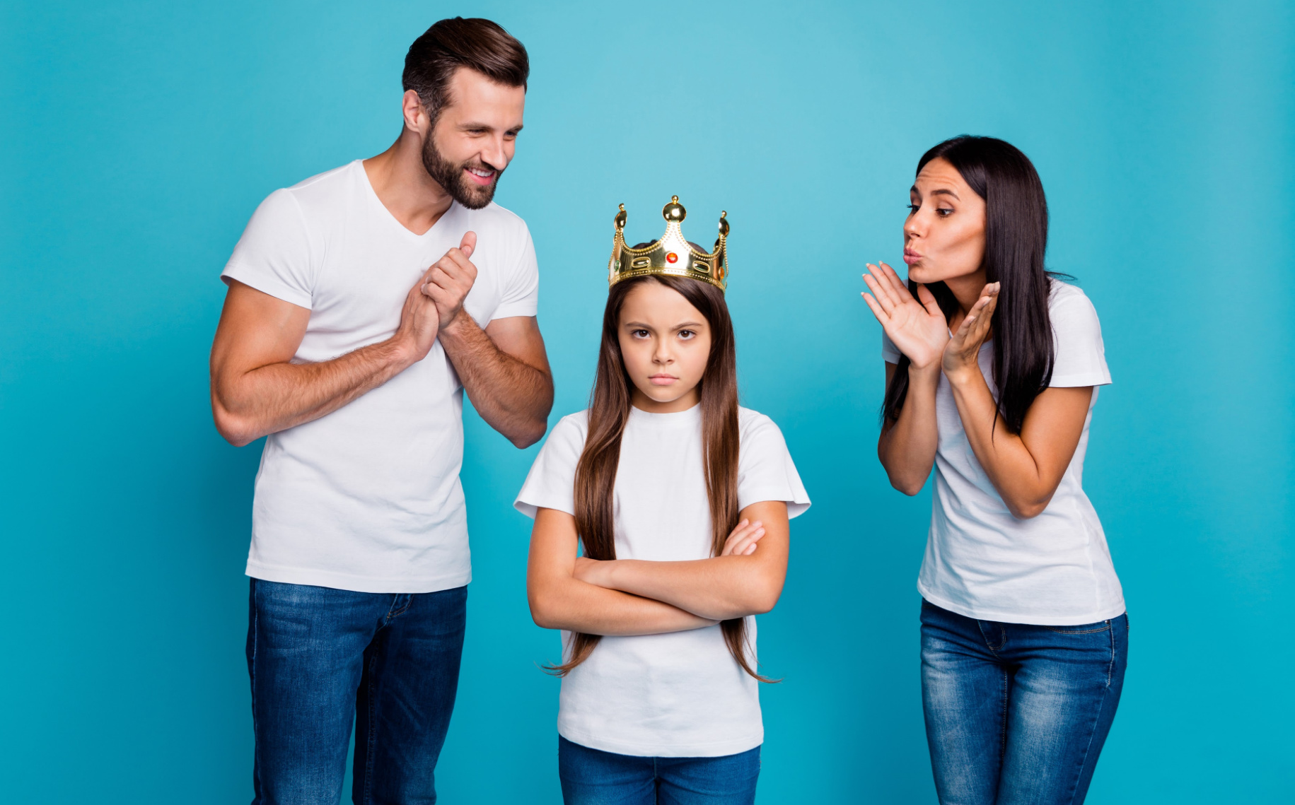 Parents fawning over child wearing a crown, arms crossed.